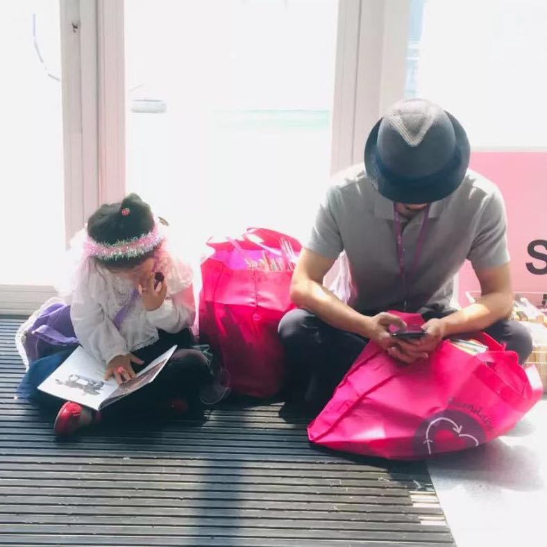 father and daughter sitting cross legged reading books on the floor