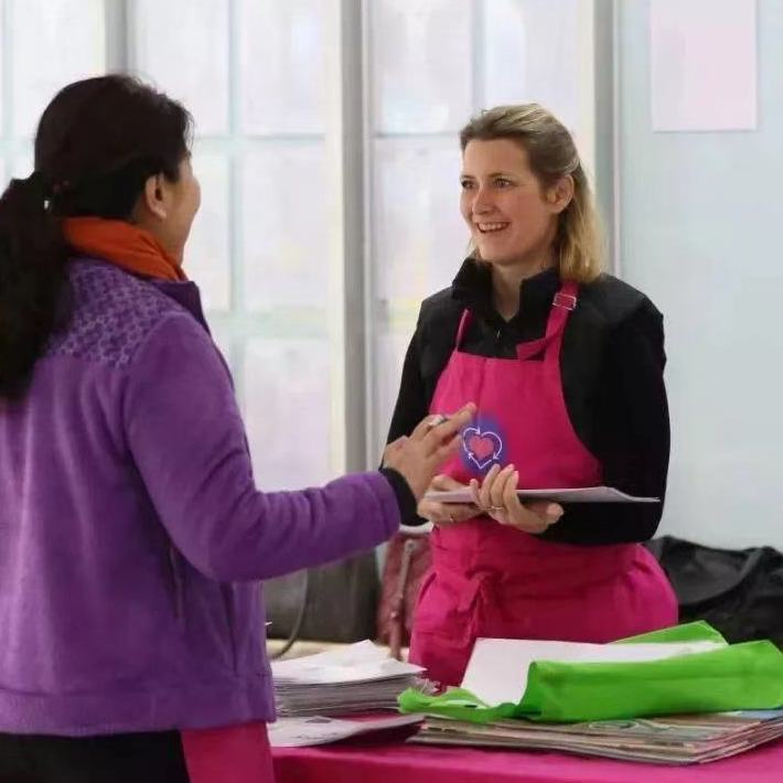 friendly caucasian woman wearing a fashionable roundabout branded hot pink apron