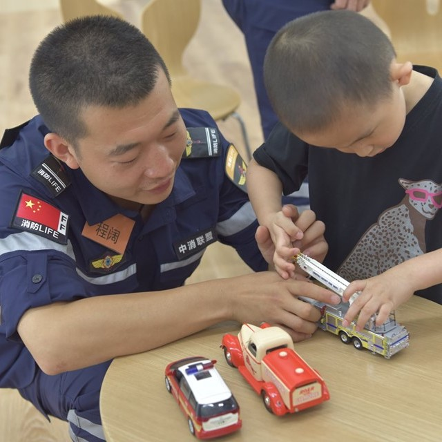 handsome chinese fireman and a small boy together playing with toy fire trucks and ambulances