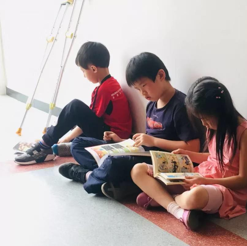 three chinese children reading comic books sitting together in a bright hallway