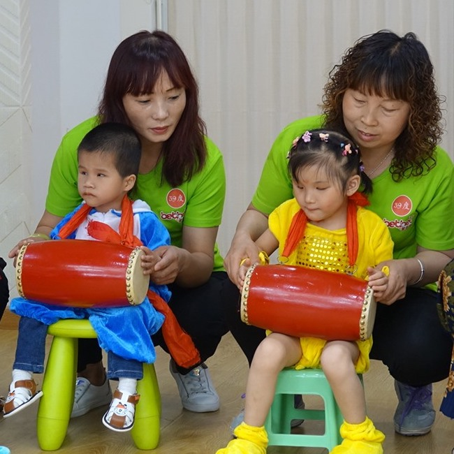 two bethel volunteers with visually impaired toddlers on their laps practicing a traditional chinese purcussive instrument