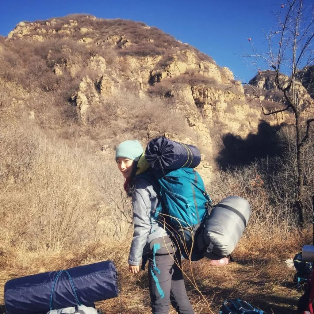 female chinese backpacker on an outdoor journey through auburn grass mountains 1024x1024