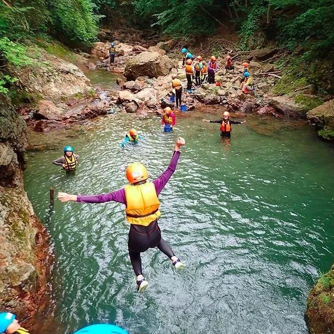 hikers wearing helmets and lifevests as they dive into a fresh body of water in the forest