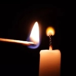 lighting a candle with a match with a jet black background