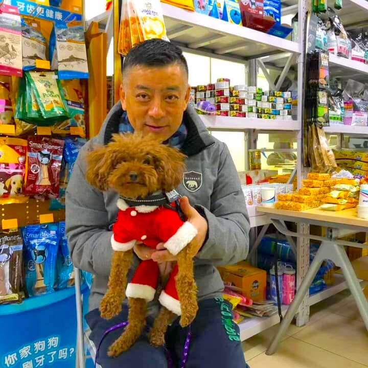male chinese dog owner holding a small dog in a santa claus costume